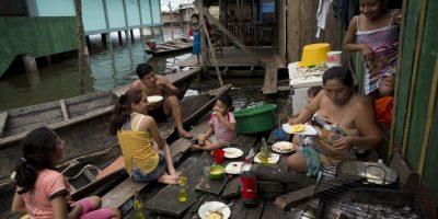 """En esta imagen del 19 de abril de 2015, la familia López Vázquez come ante su casa, que se alza a escasa distancia del agua de las crecidas del río Itaya, a la entrada de IBelén, una empobrecida comunidad peruana conocida como """"Venecia de la jungla"""" en Iquitos, Perú. La vida aquí cambia entre julio y diciembre, cuando el río retrocede a su nivel más bajo. Foto:AP/ Rodrigo Abd"""