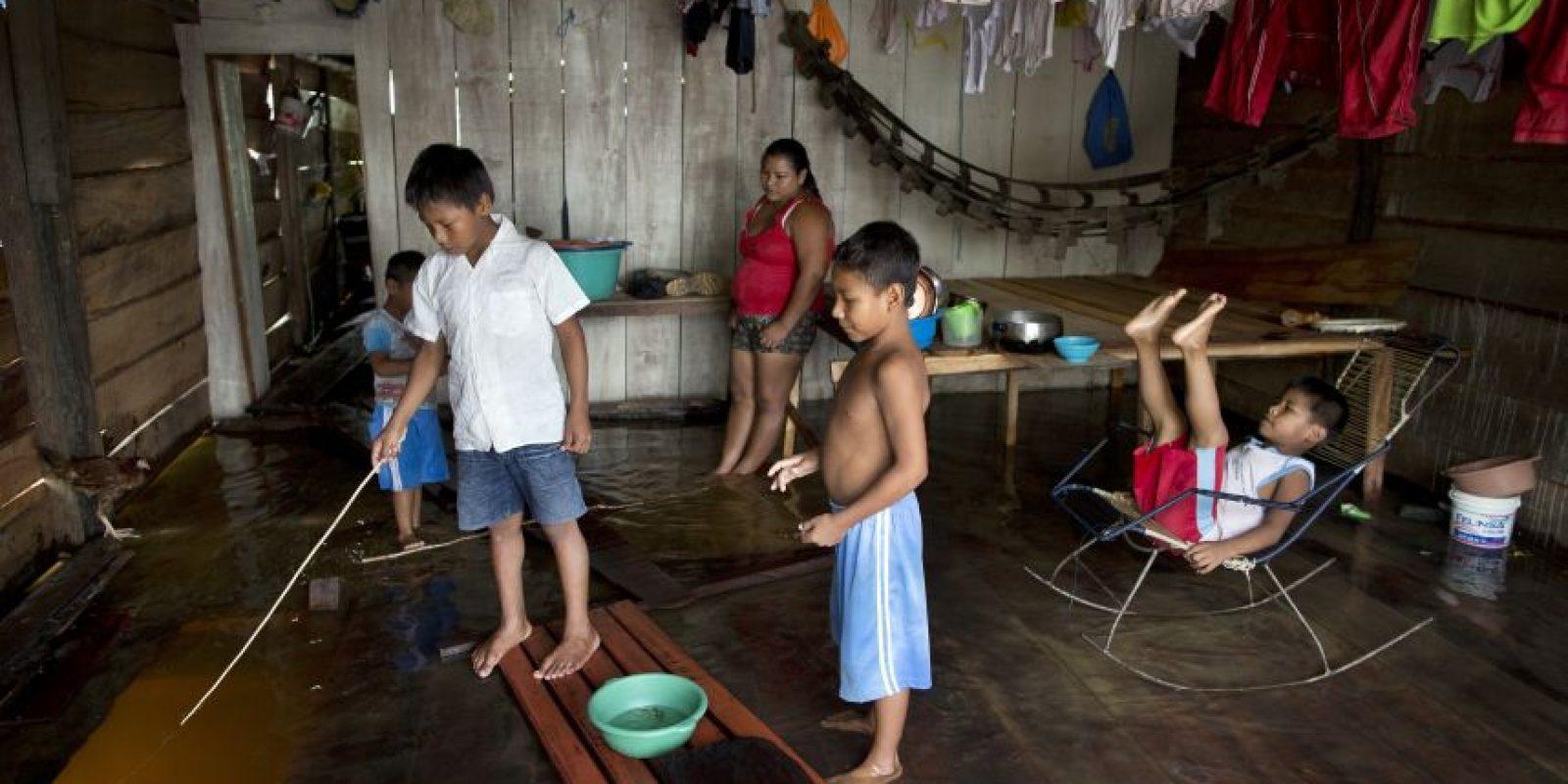 """En esta imagen del 9 de abril de 2015, Darío Tamani, de 10 años, pesca dentro de su caasa, inundada por la subida del río, en el barrio de Belén en Iquitos, Perú, una empobrecida comunidad peruana conocida como """"Venecia de la jungla"""". De enero a junio, el agua de las crecidas de un afluente del Amazonas inunda la población y cambia de forma drástica la vida cotidiana. Hay agua por todas partes, lo que permite incluso pescar desde las casas a través de un agujero en el suelo. Foto:AP/ Rodrigo Abd"""
