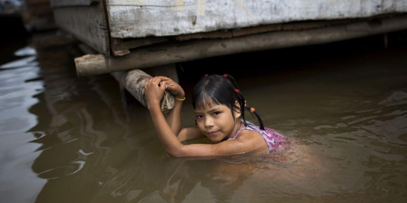 """En esta imagen del 19 de abril de 2015, una niña agarrada a los cimientos de su casa en Belén, una empobrecida comunidad peruana conocida como """"Venecia de la jungla"""" en Iquitos, Perú. Los chicos en edad escolar van a clase en pequeñas embarcacioens, y a menudo nadan y juegan en el agua tras llegar a casa. Foto:AP/ Rodrigo Abd"""