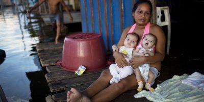 """En esta imagen del 20 de arbil de 2015, Graciela Shuna, de 33 años, sentada ante su casa con sus gemelas de cuatro meses, Mía y Galena, en Belén, una empobrecida comunidad peruana conocida como """"Venecia de la jungla"""" en Iquitos, Perú.Las madres vigilan con atención a los niños pequeños que aprenden a andar en esta época del año, y la prensa local informa de uno o dos pequeños que mueren ahogados cada año. Foto:AP/ Rodrigo Abd"""