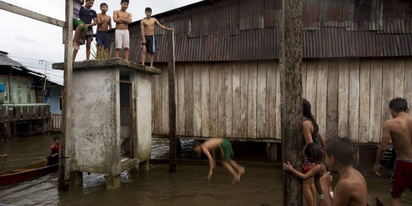 """En esta imagen del 19 de abril de 2015, niños jugando en las calles inundadas de Belén, una empobrecida comunidad peruana conocida como """"Venecia de la jungla"""" en Iquitos, Perú.. La vida en este vecindario cambia de julio a diciembre, cuando el río Itaya se retira a su nivel más bajo y el calor del verano seca las calles. Foto:AP/ Rodrigo Abd"""