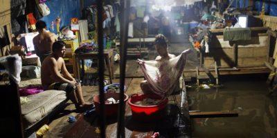 """En esta imagen del 20 de abril de 2015, Milagros Chumbe lava la ropa dentro de su casa inundada en Belén, una empobrecida comunidad peruana conocida como """"Venecia de la jungla"""" en Iquitos, Perú. Dieciéis miembros de tres familias distintas viven en la casa, inundada por las crecidas del río Itaya. Durante la temporada de lluvias, las madres vigilan de cerca a los pequeños que aprenden a caminar para asegurarse de que no caen al agua, y la prensa local informa cada año de la muerte de uno o dos niños ahogados. Foto:AP/ Rodrigo Abd"""