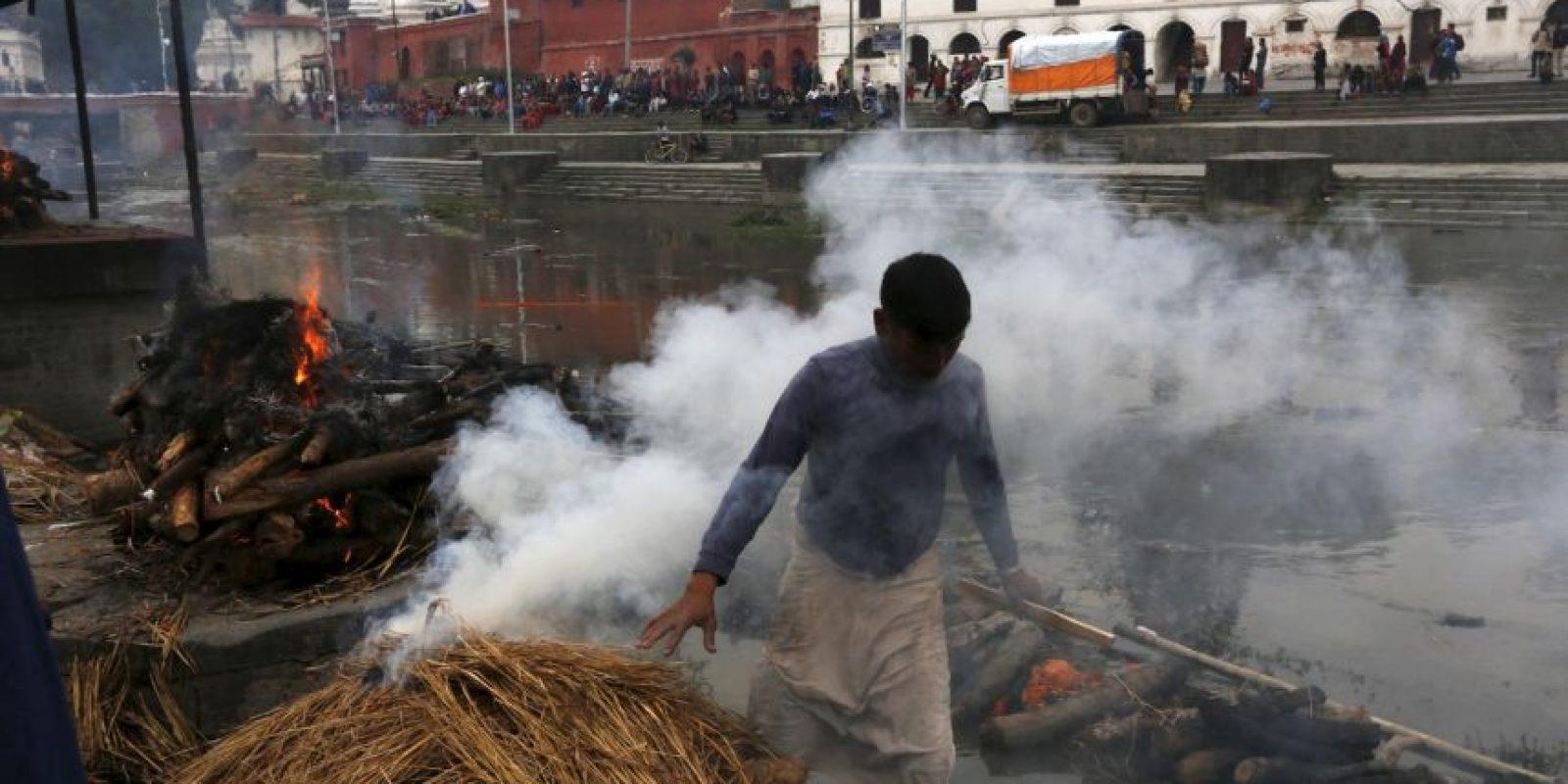 Los voluntarios se enfrentan a la difícil tarea de quemar los cuerpos de las víctimas del terremoto Foto:AP