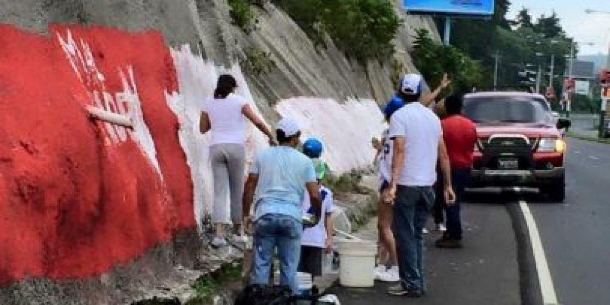 FOTOS. Borran propaganda de Líder de un muro de contención