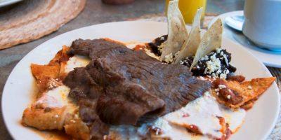 Una comida mexicana de tortilla frita sumergida en salsa o mole, tradicionalmente acompañados con queso y otros acompañantes (como cebolla, pollo o huevos revueltos) Foto:Wikimedia.org