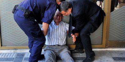 Un pensionado llora afuera de un banco Foto:AFP