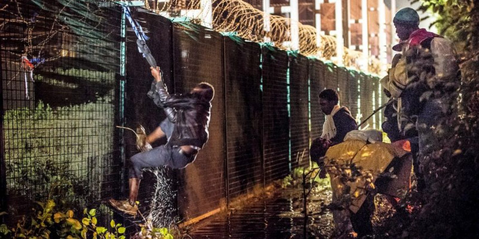 Migrante brinca valla de seguridad en Francia. Foto:AFP