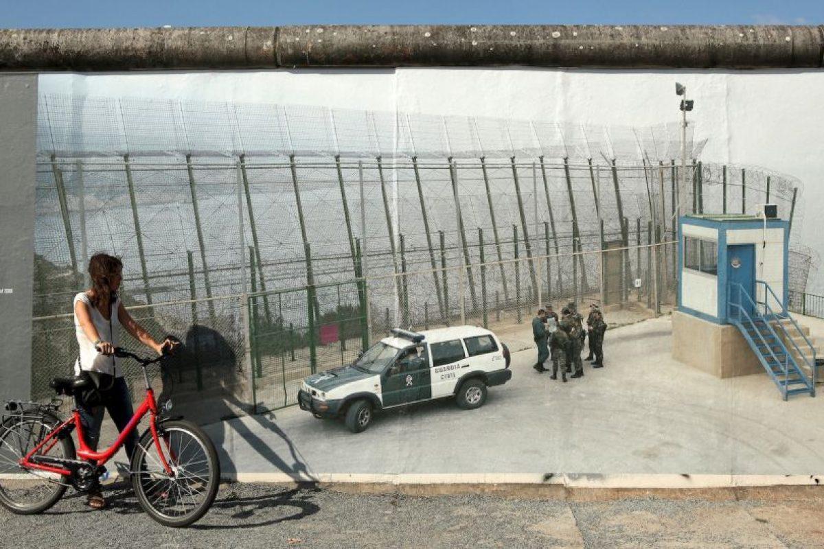 Mujer frente una foto del muro de España y Marruecos Foto:Getty Images