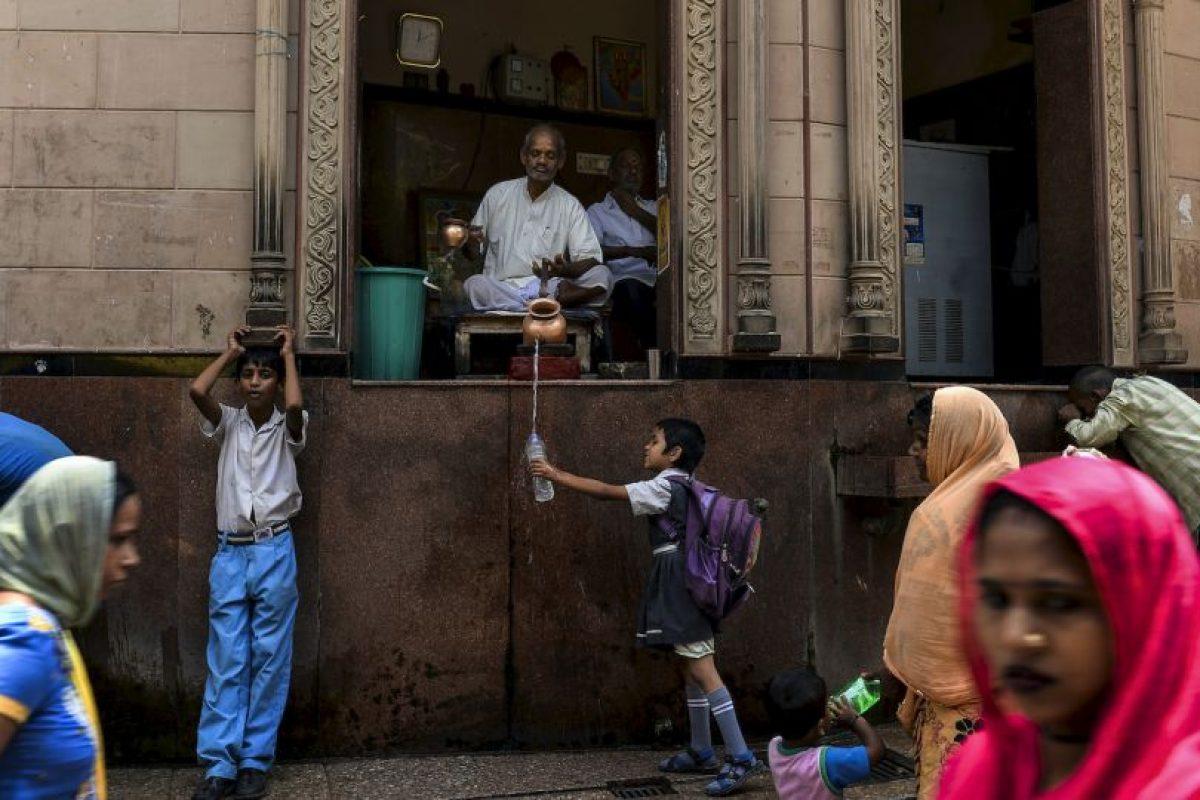 Sacerdote indio le da agua a ua niña en Nueva Delhi. Foto:AFP