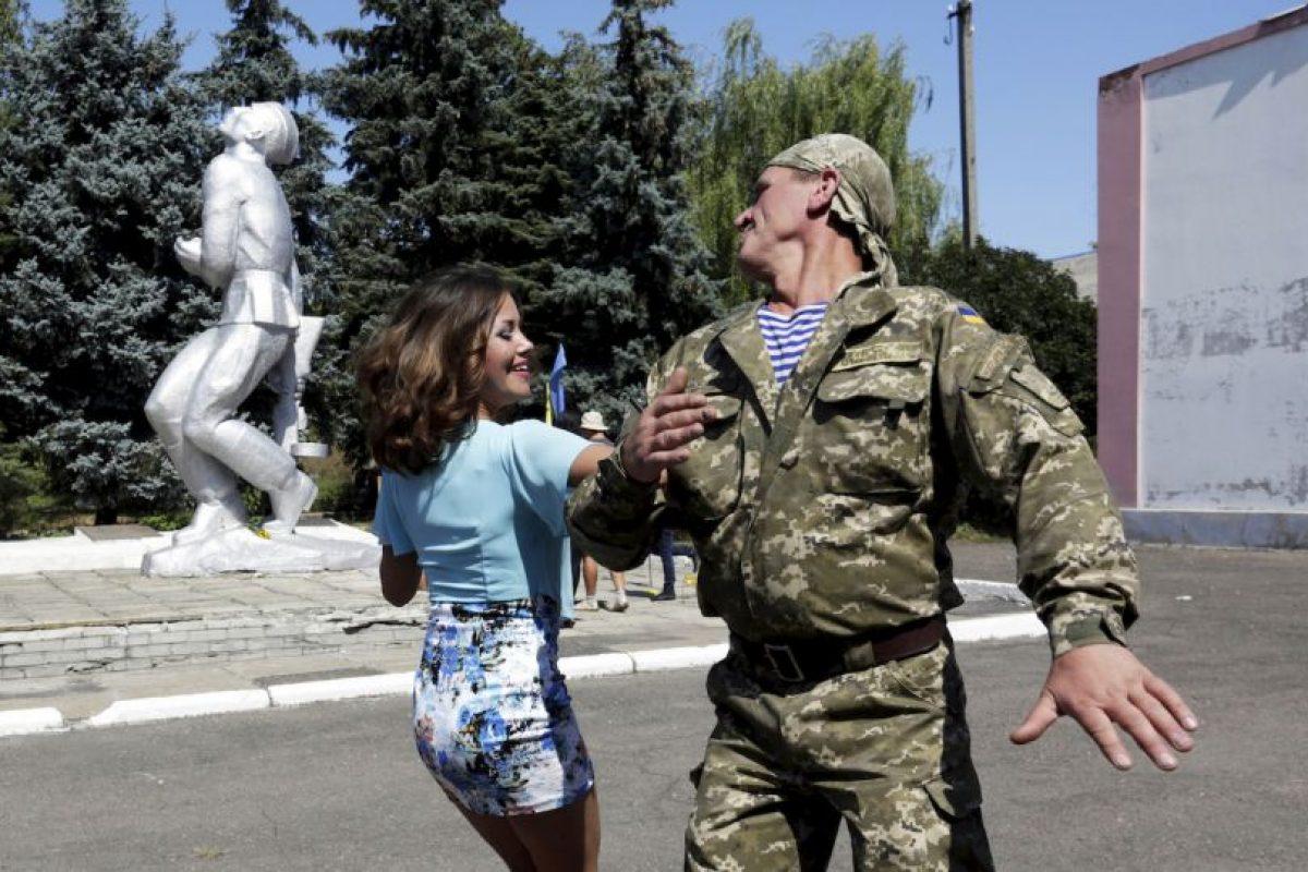 Un oficial ucraniano baila con una mujer durante el Día de Ucrania. Foto:AFP