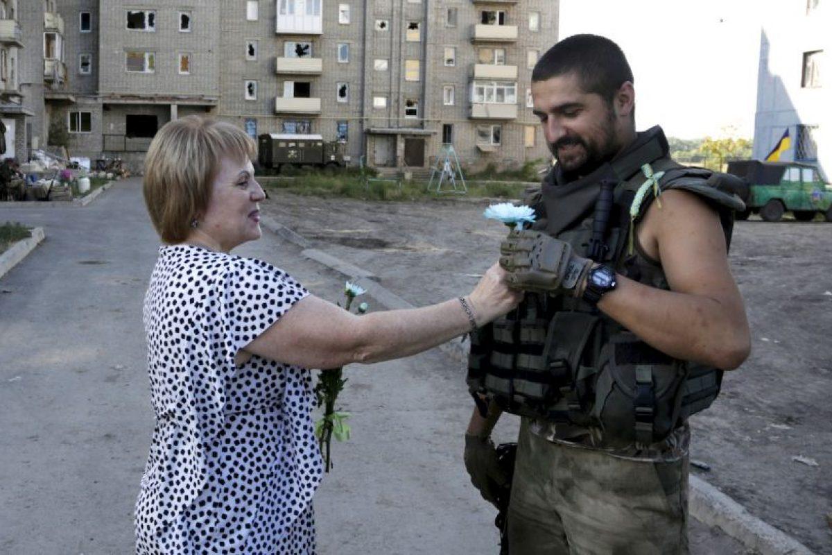Mujer le regala una flor a un oficial en Ucrania. Foto:AFP