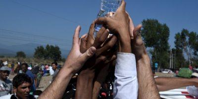 Inmigrantes intentan atrapar una botella de agua en la frontera de Macedonia y Grecia. Foto:AP