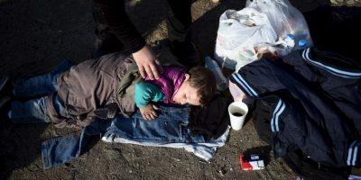Madre despierta a su hijo para continuar el trayecto en la frontera entre Macedonia y Grecia. Foto:AP