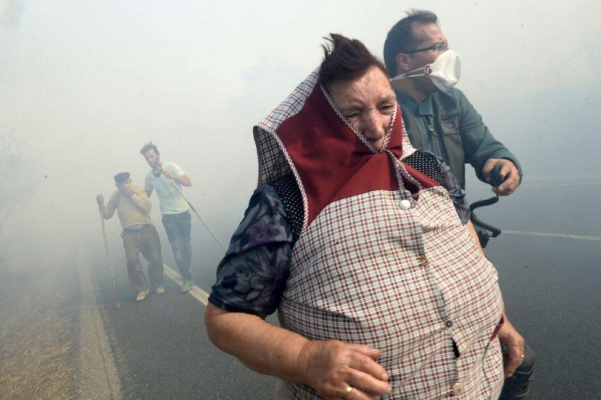 Españoles huyen del humo provocado por un fuego forestal. Foto:AFP