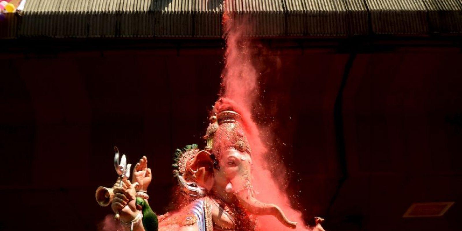 Devotos indios lanzan pétalos y polvo de color al ídolo Ganesha en una procesión en la India. Foto:AFP