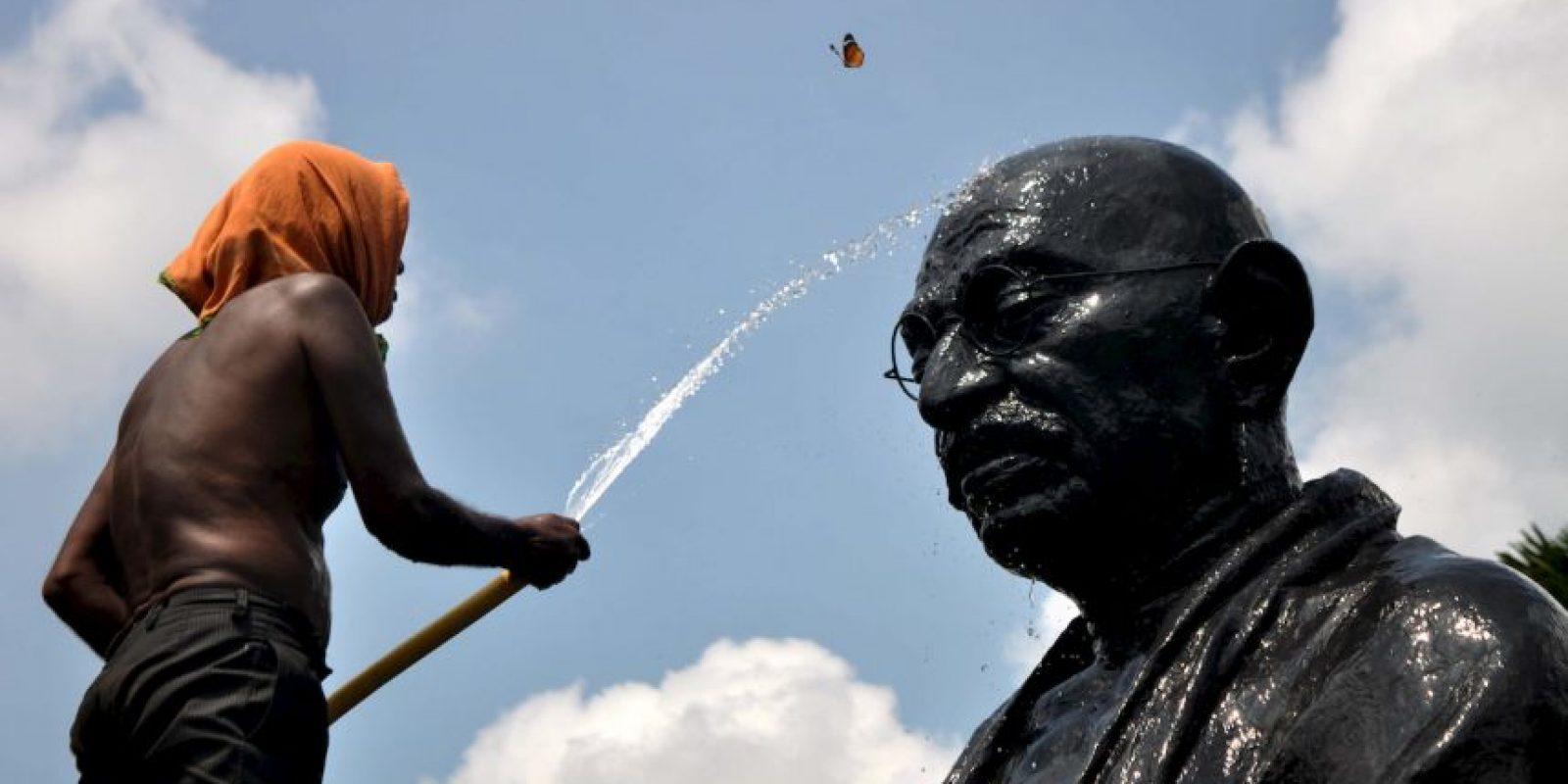 Una mariposa pasa mientras un hombre lava una estatua de Gandhi. Foto:AFP