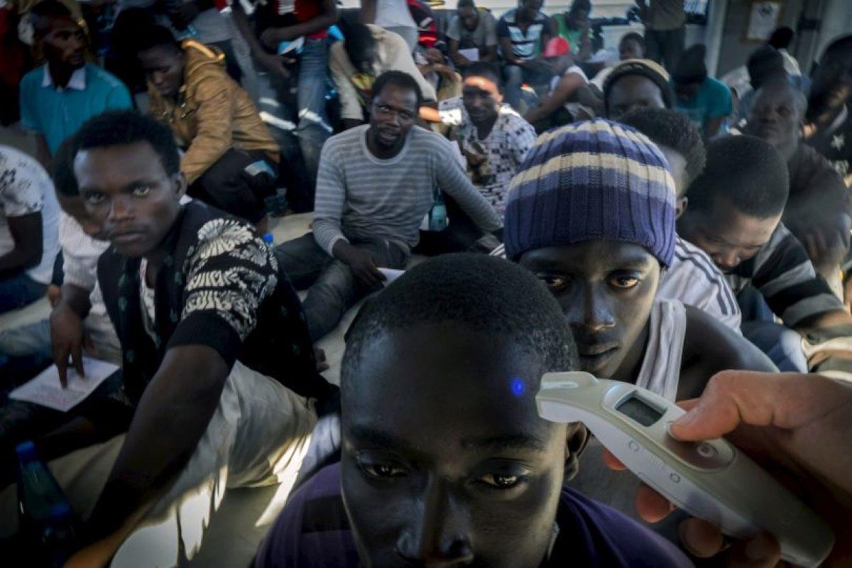 Miembros de Médicos Sin Fronteras verifican la temperatura de refugiados que llegan de Libia. Foto:AFP