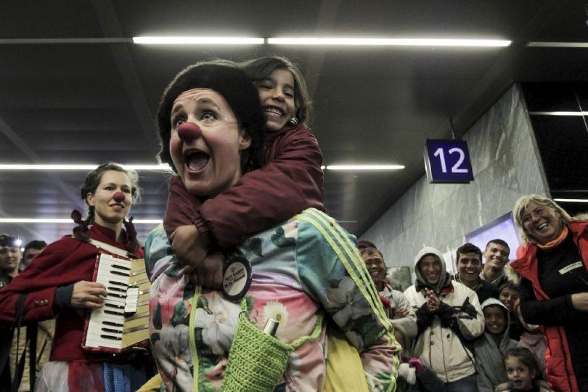 Miembros de Red Nose Clown doctors' juegan con migrantes. Foto:AFP