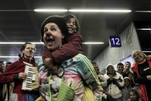 Miembros de Red Nose Clown doctors' juegan con migrantes. Foto: AFP
