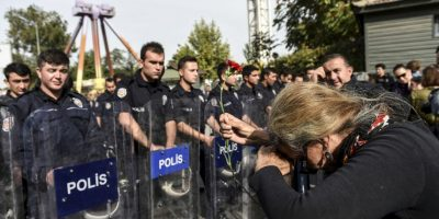 Mujer trata de llevar una flor en el lugar donde se llevaron los atentados en Turquía. Foto:AFP