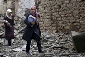 Jóvenes estudiantes sirias caminan cerca de edificios destruidos. Foto:AFP