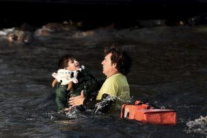 Un salvavidas español logra sacar del agua a un niño que viajaba en el bote que se hundió cerca de la isla griega Lesbos. Foto:AFP