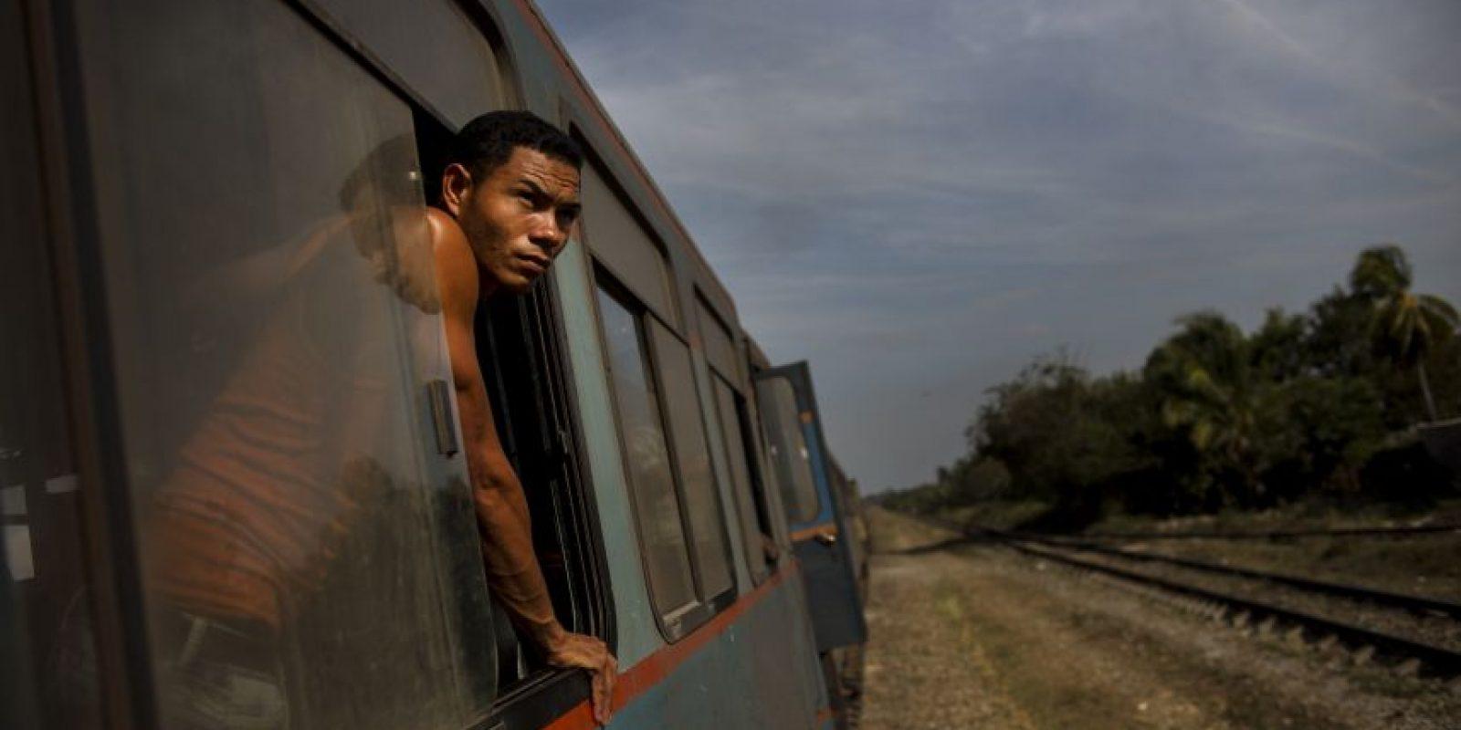 En esta fotografía del 23 de marzo de 2015, un pasajero de un tren se asoma por una ventana para ver la campiña entre Ciego de Ávila y Santa Clara, Cuba. Aunque la isla está modernizando lentamente su sistema ferroviario, sigue siendo la forma más lenta de desplazarse en Cuba, que ya de por sí se mueve lentamente. Foto:AP Photo/ Ramón Espionsa