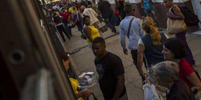 En esta fotografía del 23 de marzo de 2015, un vendedor ambulante vende dulces caseros a los viajeros en una estación de tren en la provincia de Ciego de Ávila en Cuba. En su mejor momento, los trenes cubanos contaban con vagón comedor y otros servicios de lujo. En la actualidad, los refrigerios provienen de los vendedores que abordan en muchas estaciones y ofrecen emparedados fríos y bebidas gaseosas. Afuera del tren también es posible comprar bocadillos. Foto:AP Photo/ Ramón Espionsa