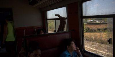 En esta fotografía del 23 de marzo de 2015, un viajero alza sus pies en un tren que viaja desde Santiago de Cuba a Santa Clara, en la provincia de Holguín, en Cuba. El recorrido desde La Habana a Santiago, a 765 kilómetros (475 millas) hacia el este, se lleva un promedio de 15 horas, si es que el tren no se descompone. Un ferrocarril ligeramente más confiable con aire acondicionado no está operando por el momento mientras es reparado. Foto:AP Photo/ Ramón Espionsa