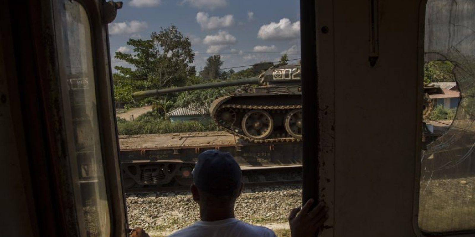 En esta fotografía del 23 de marzo de 2015, un hombre mira un tanque que está siendo transportado en un tren de carga detenido, mientras viaja en ferrocarril a través de la provincia de Holguín, en Cuba. El sistema ferroviario sufrió junto con gran parte de la infraestructura del país cuando la desaparición de la Unión Soviética dejó a Cuba sin los subsidios que Moscú había inyectado a su economía. El añejo embargo comercial estadounidense dificultó obtener refacciones. Foto:AP Photo/ Ramón Espionsa