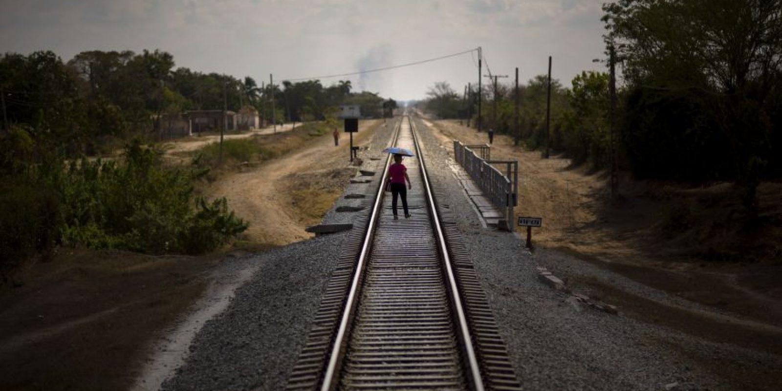 n esta fotografía del 23 de marzo de 2015, una mujer que se acaba de bajar del tren usa las vías para cruzar un puente tras llegar a su destino en la provincia de Holguín, Cuba. El país se convirtió en el primero de Latinoamérica en tener un sistema ferroviario a mediados del siglo XIX cuando la España colonial comenzó a conectar La Habana con las regiones azucareras afuera de la capital. La red creció a 9.000 kilómetros (5.600 millas) de vías que recorrían la isla hasta que paulatinamente el sistema quedara en mal estado. En la actualidad, el embargo comercial estadounidense dificulta obtener refacciones. Foto:AP Photo/ Ramón Espionsa