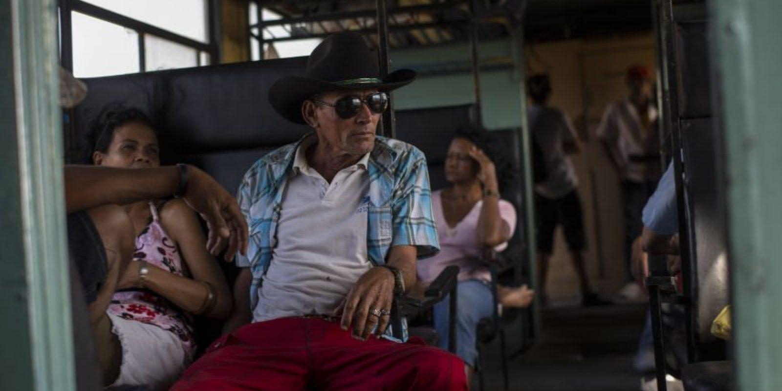 En esta fotografía del 23 de marzo de 2015, un vaquero viaja en tren a Santa Clara para participar en un rodeo mientras el tren se desplaza por la provincia de Holguín, en Cuba. De este a oeste, los trenes ofrecen una vista de Cuba en cámara lenta y alta definición que pocos extranjeros ven alguna vez. Foto:AP Photo/ Ramón Espionsa