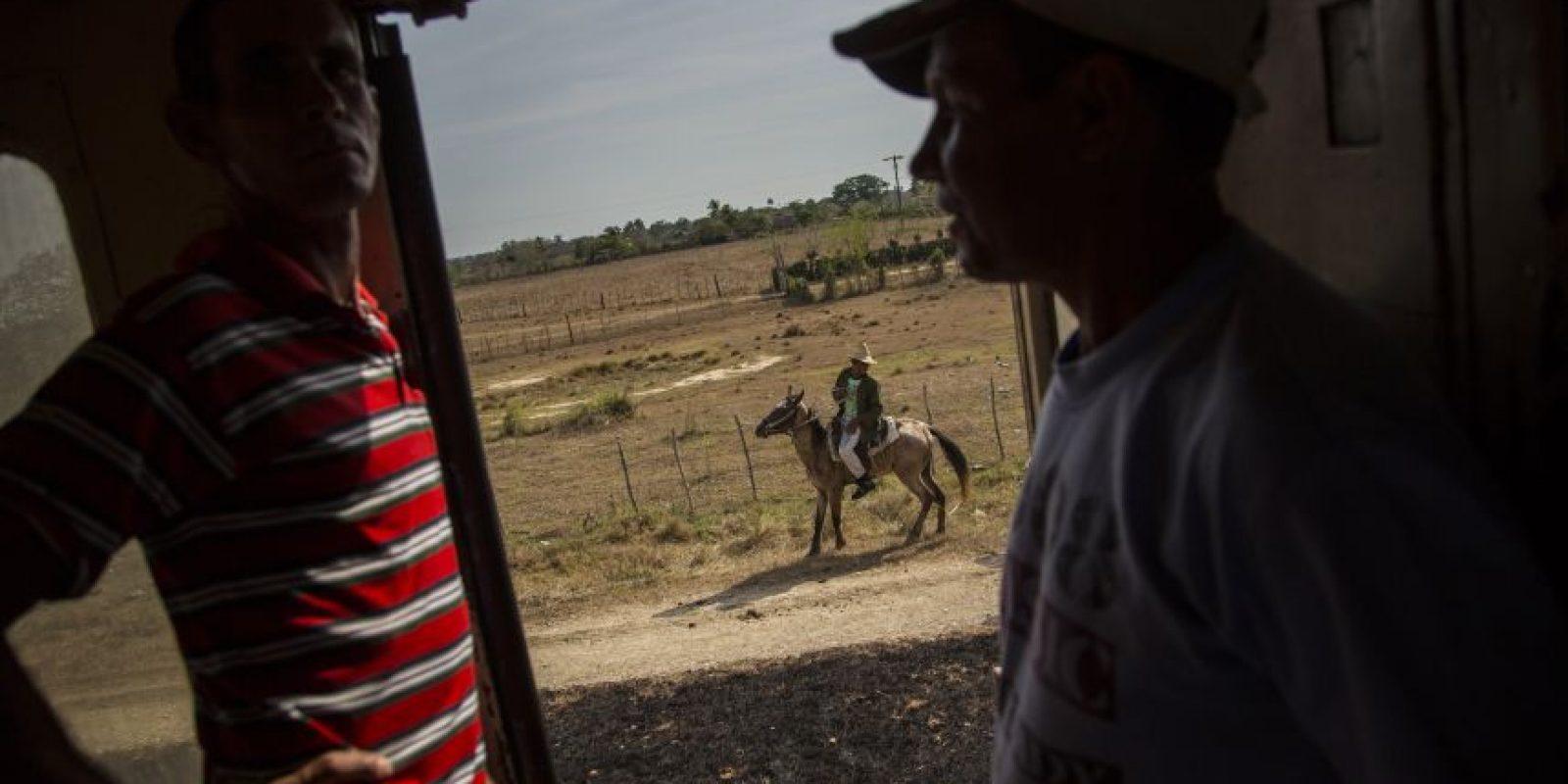 En esta fotografía del 23 de marzo de 2015, un par de pasajeros charlan en un tren mientras un granjero monta su caballo junto a las vías en la provincia de Holguín en Cuba. El país se convirtió en el primero en Latinoamérica en tener un sistema ferroviario a mediados del siglo XIX cuando la España colonial comenzó a conectar La Habana con las regiones azucareras afuera de la capital. Foto:AP Photo/ Ramón Espionsa