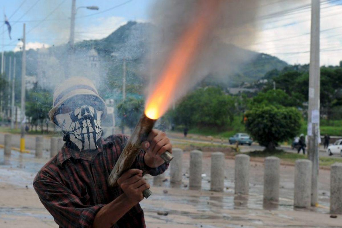 Estudiante de la Universidad Nacional Autónoma de Honduras (UNAH) disparando un arma casera. Los manifestantes han pedido la renuncia del presidente uan Orlando Hernández. Foto:AFP