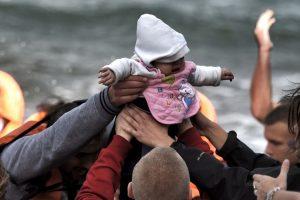 Migrantes y refugiados cargan a una bebé al llegar a la isla griega Lesbos. Foto:AFP