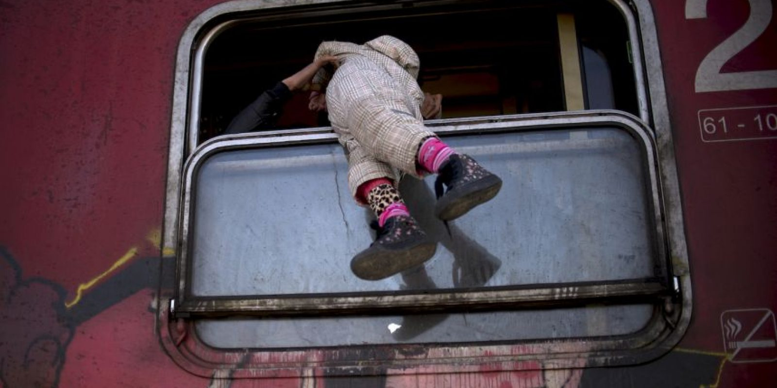 Migrante carga a niña por la ventana del tren camino a Serbia. Foto:AFP