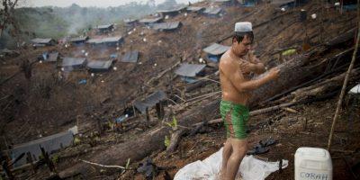 En esta imagen del 28 de octubre de 2015, Waldir Rodríguez, contratado para destruir cosechas ilegales de coca, se da una ducha mañanera en el campo base establecido por el Proyecto Especial de Control y Reducción de Cultivos Ilegales en el Alto Huallaga (CORAH) en un campo quemado por agricultores locales en Nueva Esperanza, un remoto pueblo en la municipalidad de Ciudad Constitución, en la Amazonia peruana. Si bien los erradicadores destruyeron 55.000 hectáreas de plantaciones de coca en el 2013 y el 2014, no han sacado un solo arbusto de la principal región productora, el valle de los ríos Apurímac, Ene y Mantaro, al sur de esta zona. Se calcula que hay 15 organizaciones traficantes de drogas en la zona. Foto:AP Photo/ Rodrigo Abd