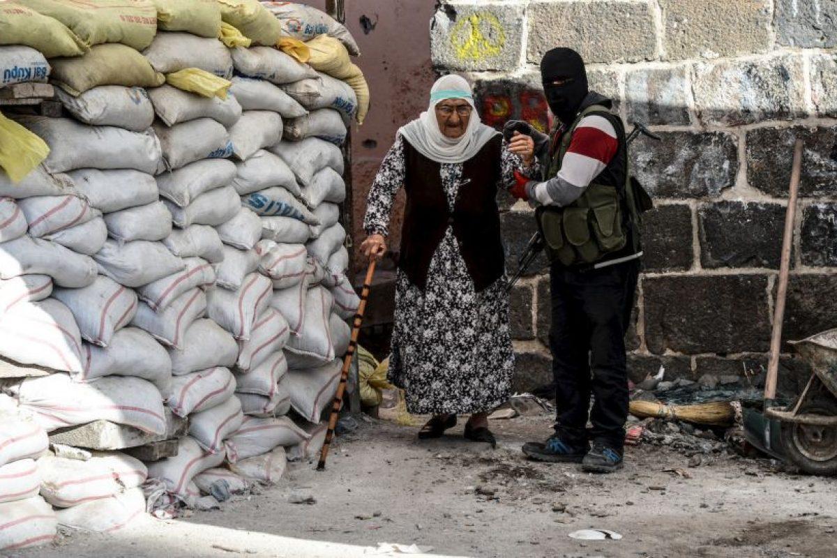 Militante kurdo ayuda a una anciana a pasar por una barricada en Turquía. Foto:AFP