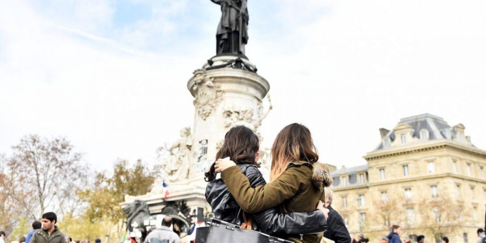 Ciudadanas se abrazan durante ceremonia de recordación en la Plaza de la República en París. Foto:AFP