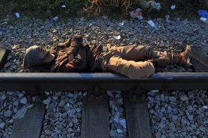 Hombre duerme sobre las vías de un tren en la frontera de Grecia y Macedonia. Foto:AFP