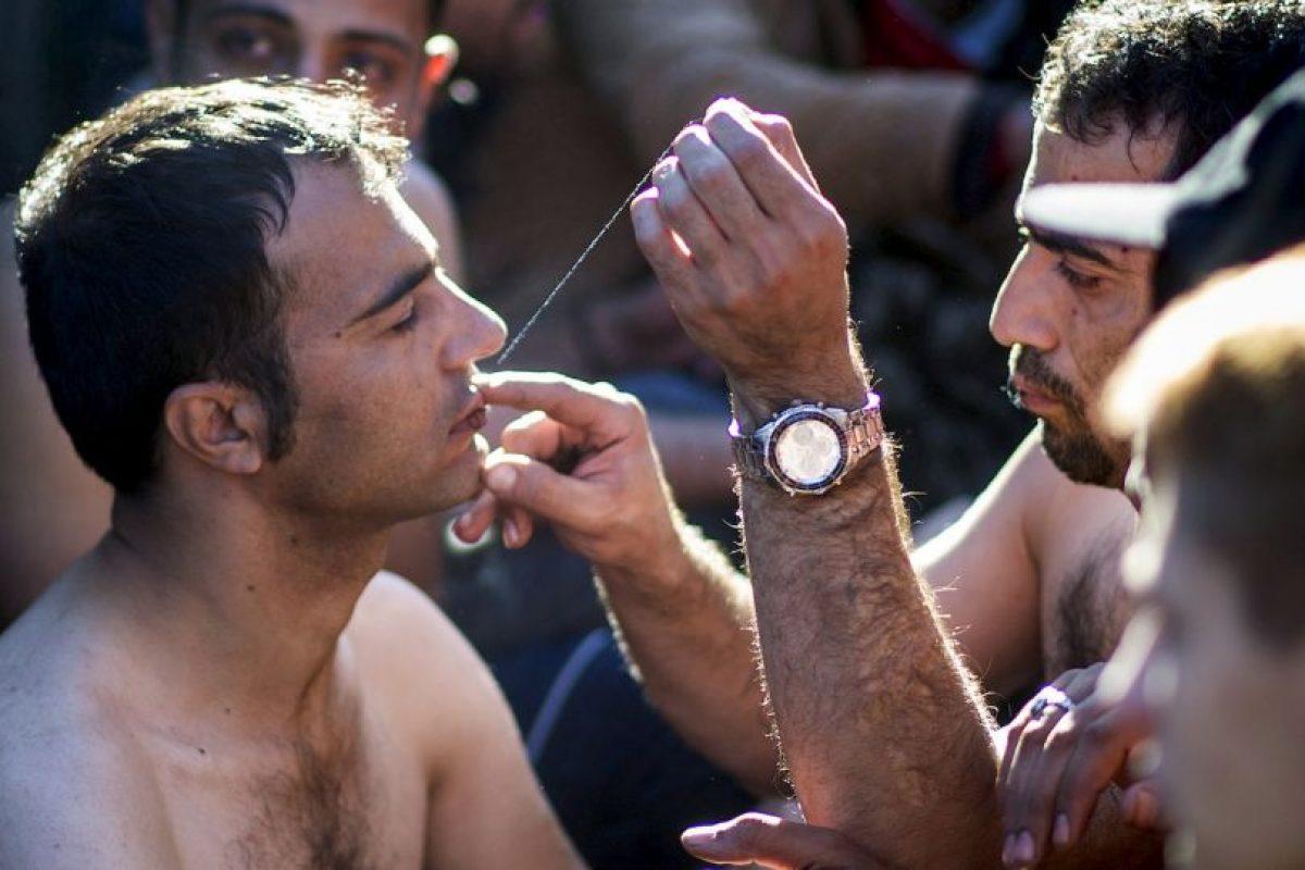 Iraníes cosiendo sus labios para la protesta. Foto:AFP
