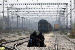 Dos hombres sentados en las vías mientras migrantes y refugiados esperan el tren en la frontera de Grecia y Macedonia. Foto:AFP