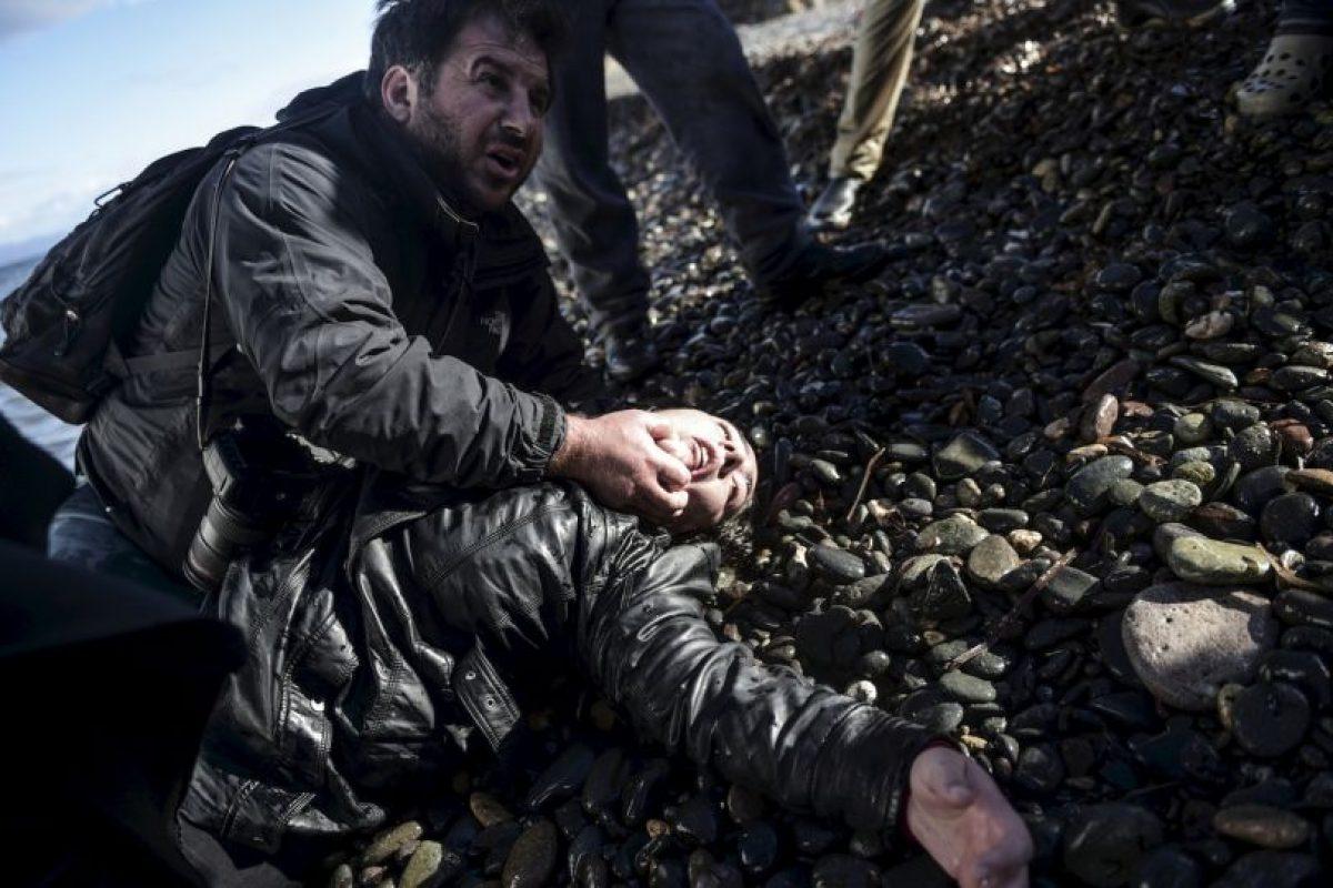 El fotógrafo Giorgos Moutafis ayuda a una migrante herida en la isla de Lesbos. Foto:AFP