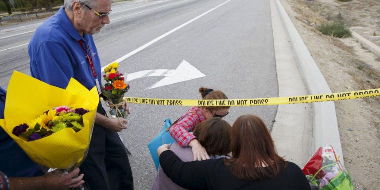 Una mujer, identificada como la prometida de una de las víctimas del atentado en California, deja flores en el lugar de los hechos. Foto:AFP
