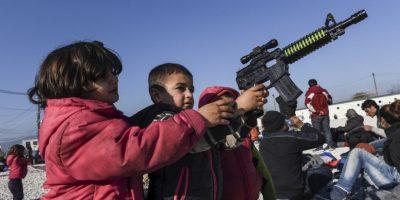 Niños juegan con un arma de mentira en la frontera de Grecia y Macedonia. Foto:AFP
