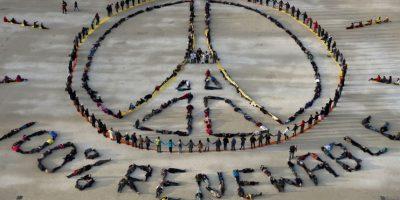 Ciudadanos hacen el símbolo de Pray for París y el de 100% renovable durante una manifestación en el marco de la Cumbre del Clima. Foto:AFP
