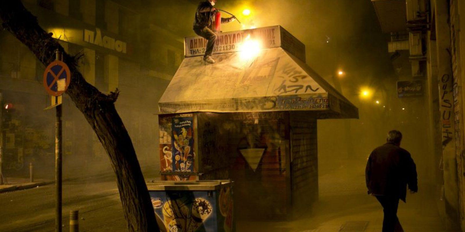Un vendedor trata de apagar un incendio en su kiosco durante los enfrentamientos entre la policía antidisturbios y manifestantes en Atenas. Foto:AFP