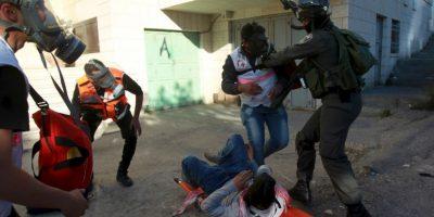 Un paramédico palestino intenta evitar que un guardia fronterizo israelí detenga al manifestante tendido en la camilla. Foto:AFP