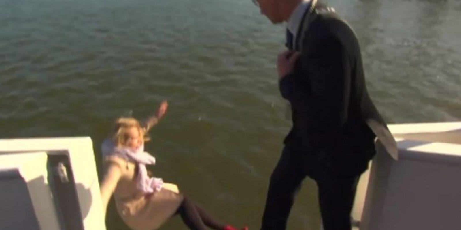 El momento en que una reportera holandesa cae al mar durante una entrevista al alcalde de la ciudad de Kampen. Foto:vía Toutube.com