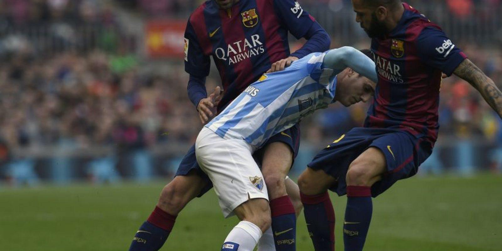 Jugadores del Málaga y Barcelona disputan el balón. Foto:AFP